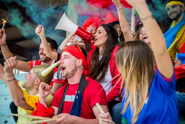 Fußballfans im stadion - fußballfans, die spaß haben und sich ein fußballspiel ansehen