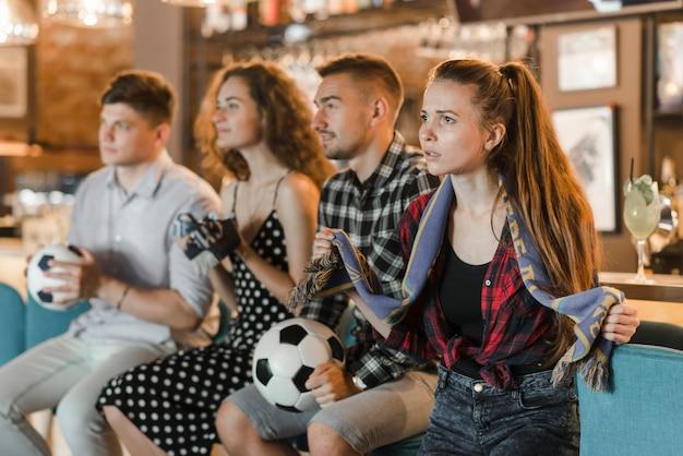 Fußballfans in der stange, die fußballspiel im fernsehen aufpasst