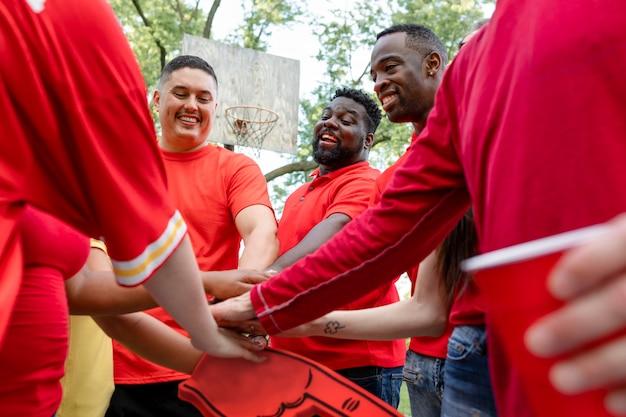 Fußballfans in einem huddle bei einer heckklappenparty Kostenlose Fotos