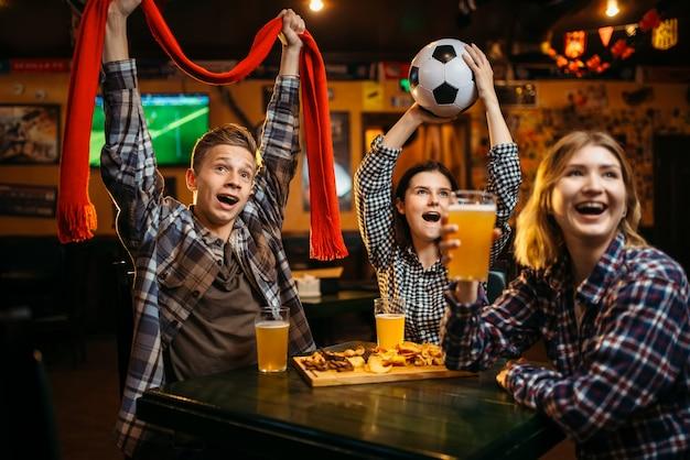 Fußballfans mit schal und ball in den händen schauen sich das spiel an und trinken bier in der sportbar.
