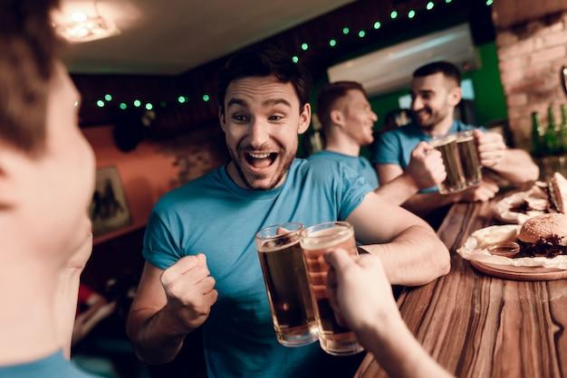 Fußballfans schauen sich das spiel mit bier an und essen.