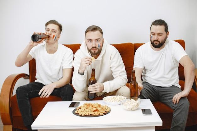 Fußballfans sitzen auf der couch im wohnzimmer und trinken bier