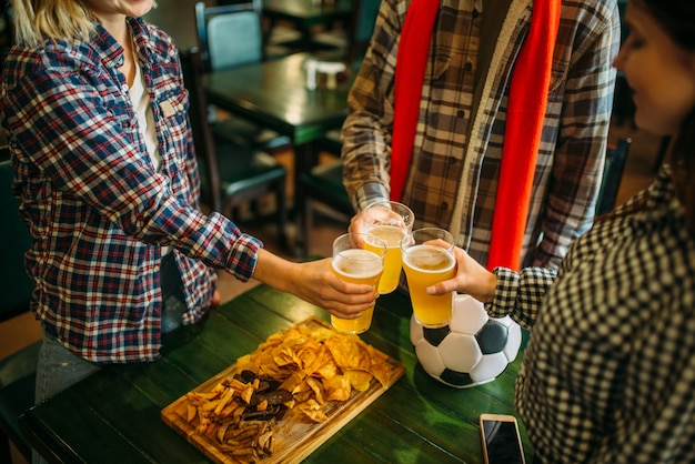 Fußballfans stoßen in der sportbar mit hellem bier an. tv-übertragung, junge freunde feiert sieg der lieblingsmannschaft, erfolgsspiel feier in der kneipe