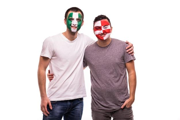 Fußballfansanhänger mit gemaltem gesicht der nationalmannschaften von nigeria und von kroatien lokalisiert auf weißem hintergrund