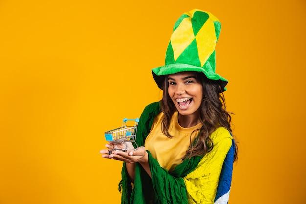Fußballförderung. frau, die einen mini-einkaufswagen in den händen hält und brasilianische kleidung trägt.
