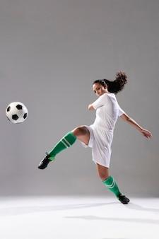 Fußballfrau, die fußball tritt