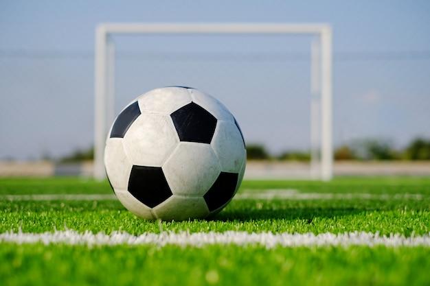 Fußballfußball auf grüner rasenfläche und torpfosten
