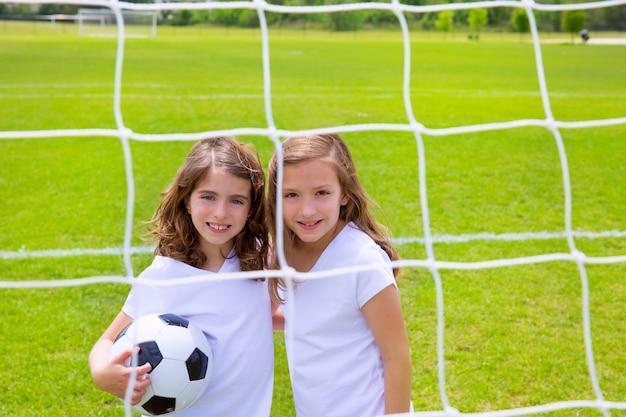 Fußballfußballkindermädchen, die auf feld spielen