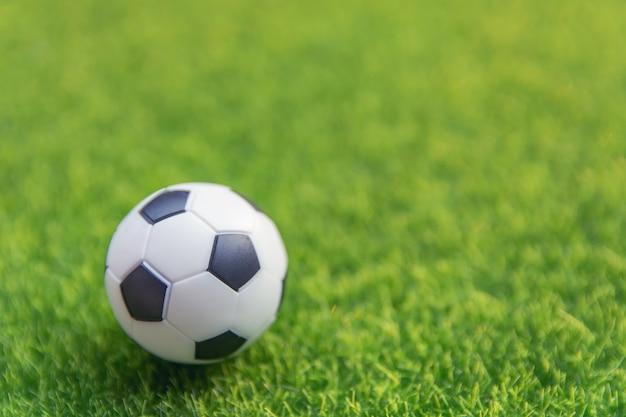 Fußballkugel auf grasgrünfeld mit kopienraum