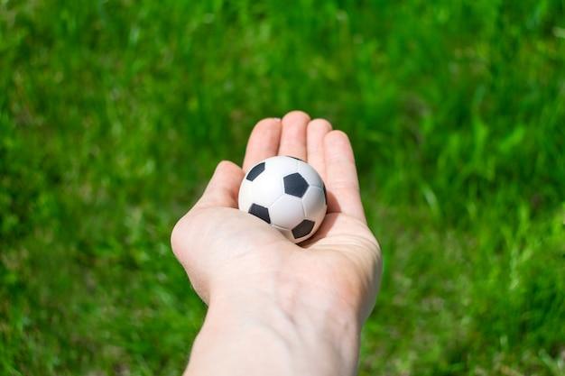 Fußballkugel in der weiblichen hand auf hintergrund des grünen grases