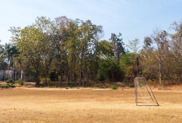 Fußballplatz und altes fußballtor auf dem dorfsportplatz am sommertag., fußballplatz an der städtischen schule. sportkonzept.