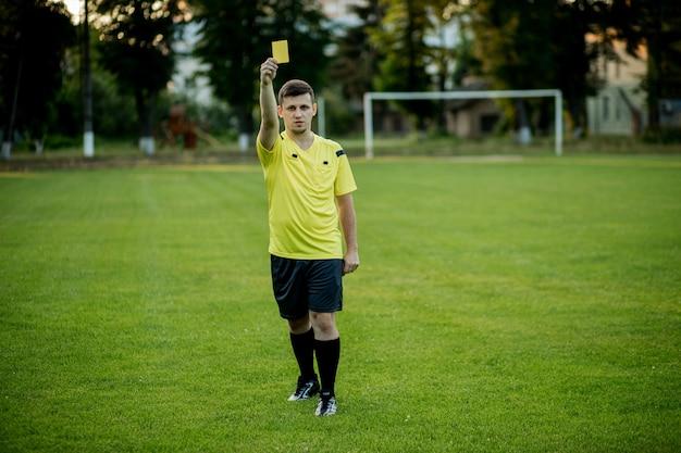Fußballschiedsrichter weist einen spieler im fußballstadion auf eine gelbe karte hin