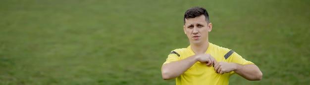 Fußballschiedsrichter weist einen spieler im fußballstadion auf eine gelbe karte hin.