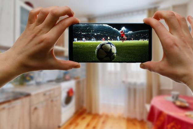 Fußballspiel zu hause über das smartphone anschauen. übertragung von fußball aus dem stadion.
