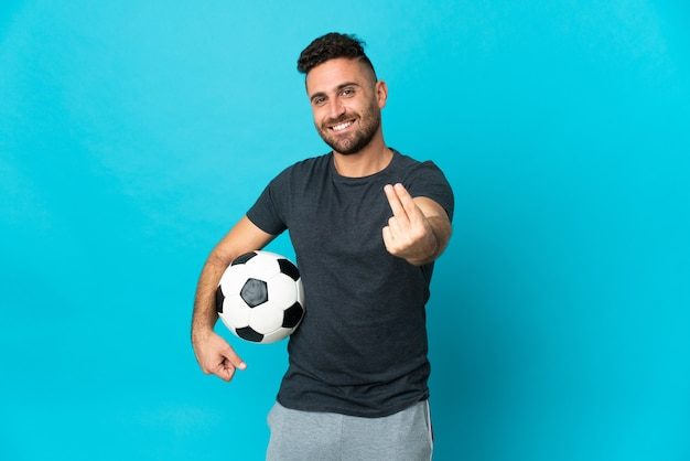 Fußballspieler auf blauem hintergrund isoliert, der geldgeste macht