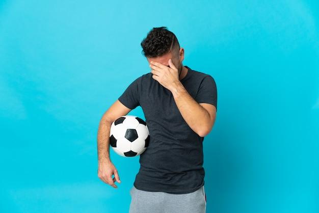 Fußballspieler auf blauem hintergrund lachend isoliert
