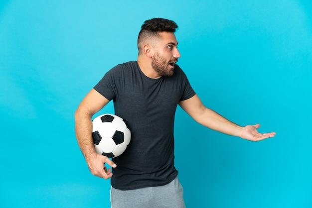 Fußballspieler auf blauem hintergrund mit überraschungsausdruck isoliert, während er zur seite schaut