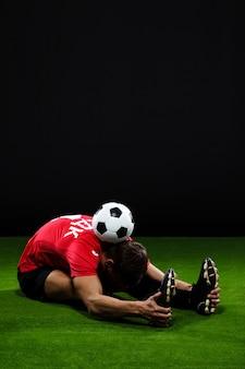 Fußballspieler, der auf gras mit ball streckt