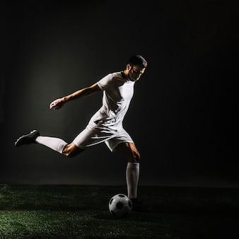 Fußballspieler, der ball schießt