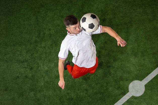Fußballspieler, der ball über grünem grashintergrund angreift