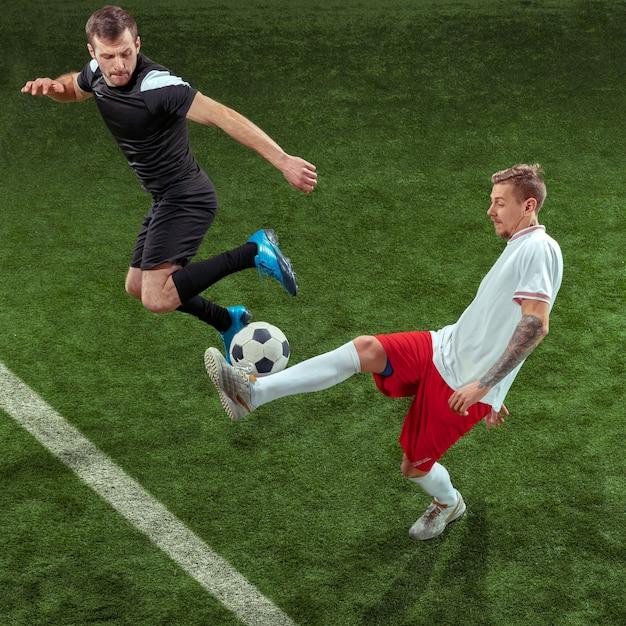 Fußballspieler, der für ball über grünem gras angreift