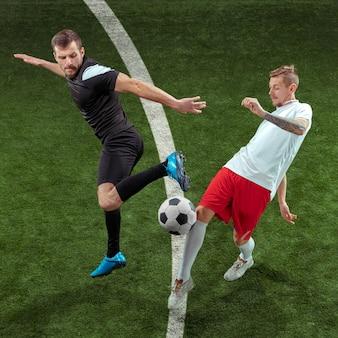 Fußballspieler, der für ball über hintergrund des grünen grases angreift. professionelle männliche fußballspieler in bewegung im stadion. fit springende männer in aktion, sprung, bewegung beim spiel.