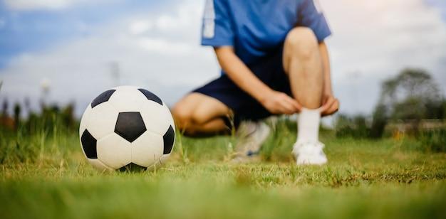 Fußballspieler, der fußball spielt, um im ländlichen gebiet der gemeinde zu trainieren?