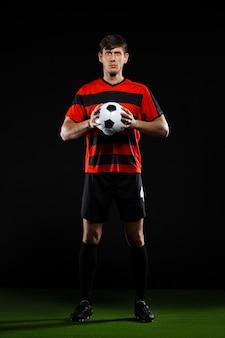 Fußballspieler, der mit ball auf grünes feld starrt