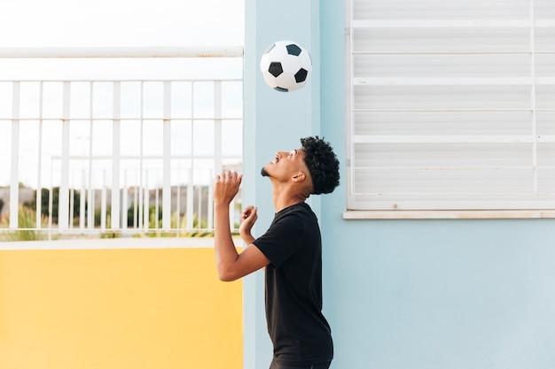 Fußballspieler, der oben ball am portal wirft