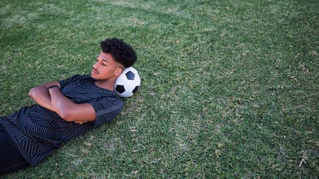Fußballspieler, der pause am fußballplatz liegt und hat
