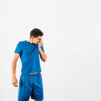 Fußballspieler, der schweiß mit t-shirt abwischt