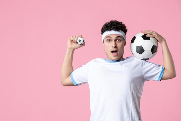 Fußballspieler der vorderansicht in der sportkleidung mit ball