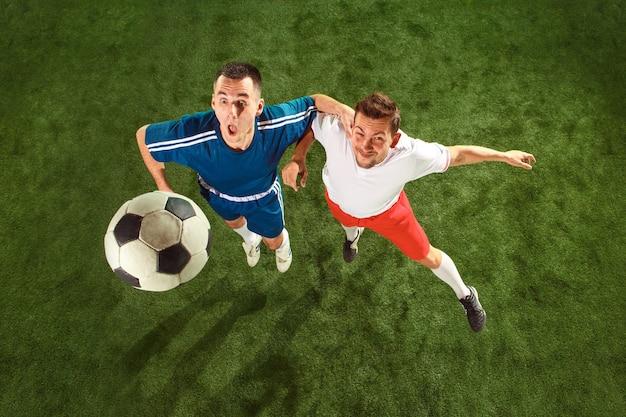 Fußballspieler, die für ball über hintergrund des grünen grases angreifen. professionelle fußballspieler in bewegung im studio. fit springende männer in aktion, sprung, bewegung beim spiel. ansicht von oben