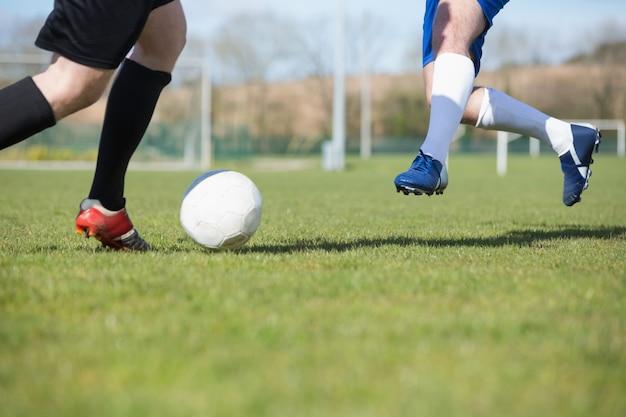 Fußballspieler, die für den ball auf neigung anpacken
