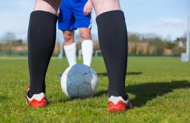 Fußballspieler, die weg auf spielfeld gegenüberstellen