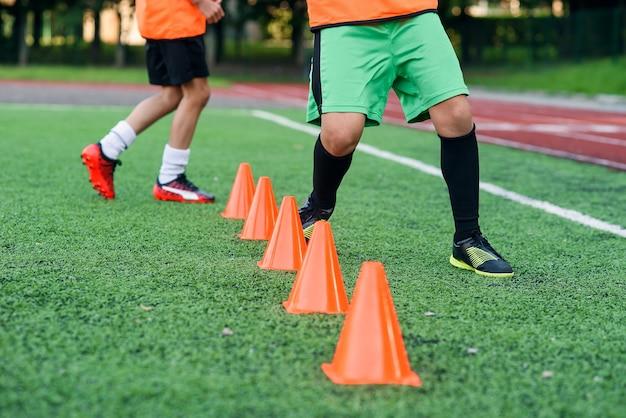 Fußballspieler, die zwischen orangefarbenen plastikkegeln laufen
