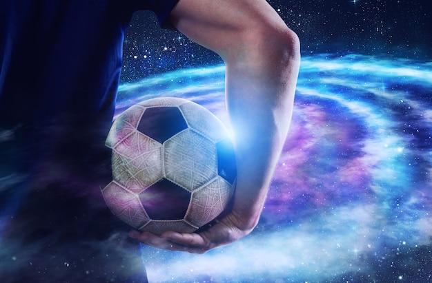 Fußballspieler hält den ball im universum