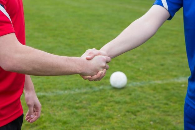 Fußballspieler im blau und im rot, die hände an einem vollen tag rütteln
