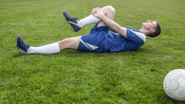 Fußballspieler im blauen lügen verletzt auf dem spielfeld