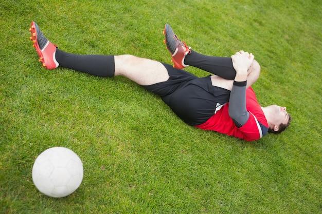 Fußballspieler im roten lügen verletzt auf dem spielfeld