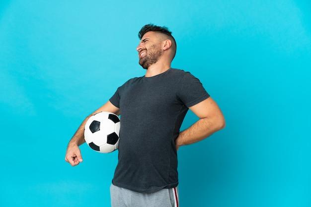 Fußballspieler isoliert auf blauem hintergrund, der an rückenschmerzen leidet, weil er sich angestrengt hat