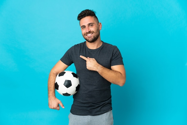 Fußballspieler isoliert auf blauem hintergrund, der auf die seite zeigt, um ein produkt zu präsentieren