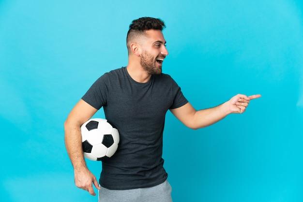 Fußballspieler isoliert auf blauem hintergrund, der mit dem finger zur seite zeigt und ein produkt präsentiert