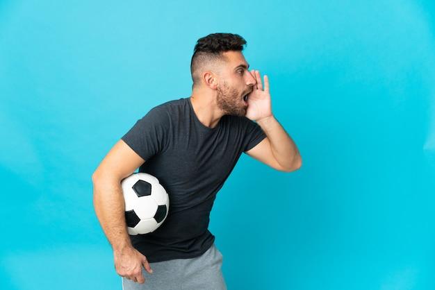 Fußballspieler isoliert auf blauem hintergrund schreien mit weit geöffnetem mund zur seite