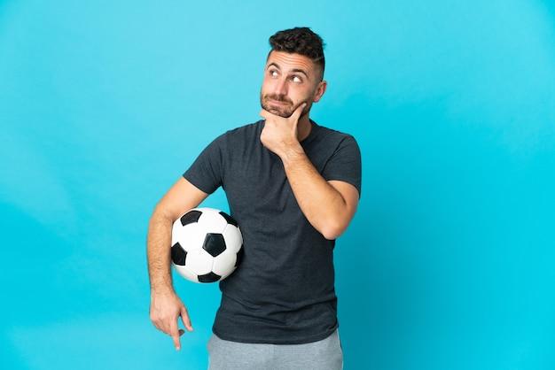 Fußballspieler isoliert auf blauer wand und nach oben schauend