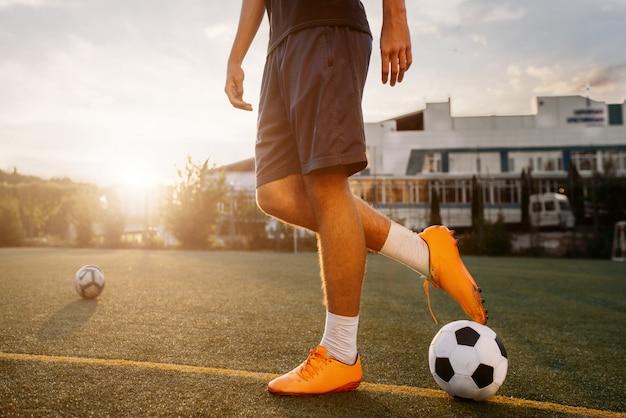 Fußballspieler mit ball auf dem feld bei sonnenaufgang. fußballer auf freiluftstadion, training vor dem spiel, fußballtraining