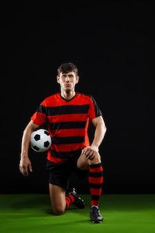 Fußballspieler mit ball, der auf knie steht, fußball spielen