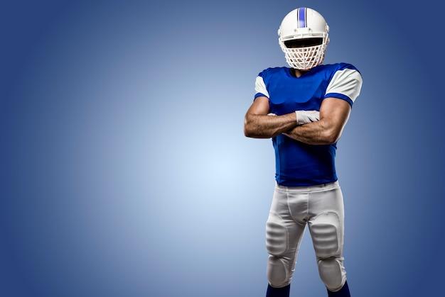 Fußballspieler mit einer blauen uniform an einer blauen wand