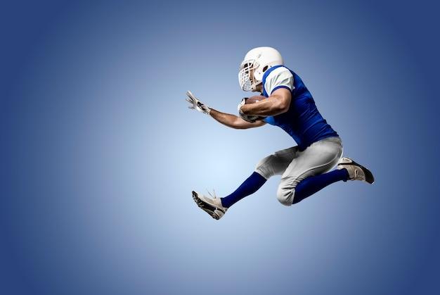 Fußballspieler mit einer blauen uniform, die auf einer blauen wand läuft