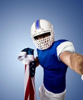 Fußballspieler mit einer blauen uniform, die ein selfie an einer blauen wand macht
